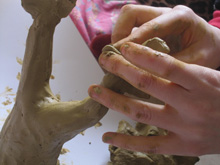 Hands working on a clay tree during art therapy